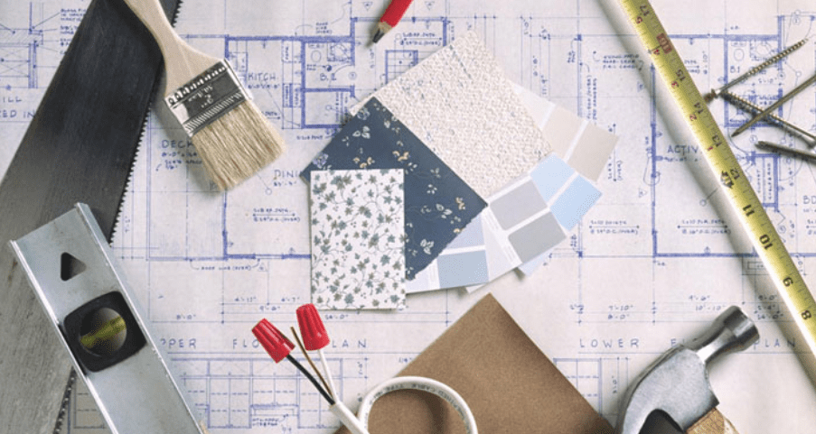 A workspace with hammer, paintbrush, ruler, blueprints, and paint samples.