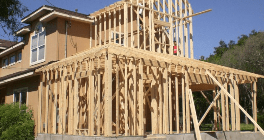 A two-story house with an addition being constructed