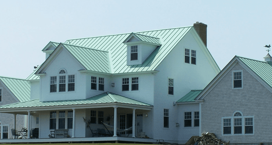 Three-story white house with green metal roof