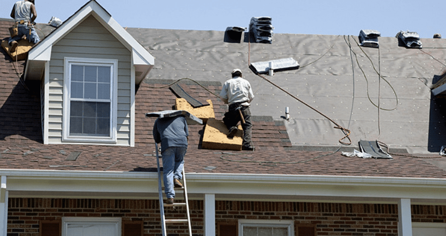 Construction workers on a half-finished two-story roof