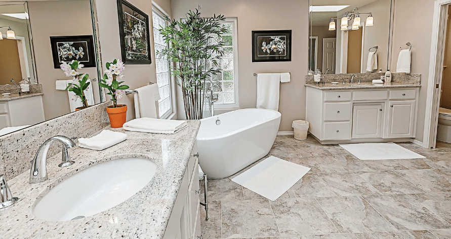 A bathroom with two sinks, bathtub, mirror, and flowers.
