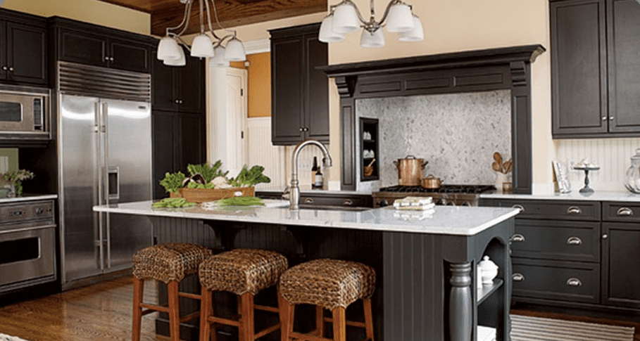 A photo of a kitchen with an island and three barstools.