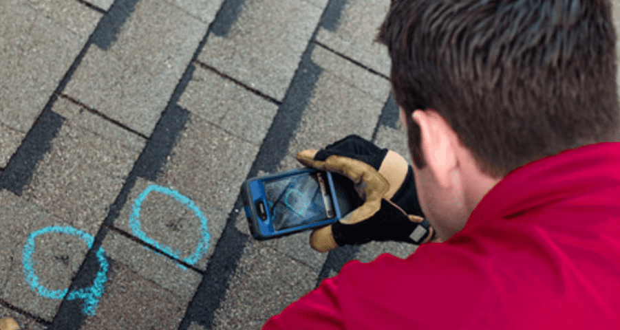 Close-up of a construction worker photographing two blue circles on a roof